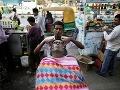 Indický pouličný holič masíruje