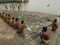 Muži sedia na brehu