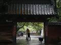 Muž zametá pred bránou