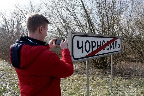 Turista si fotografuje tabuľu