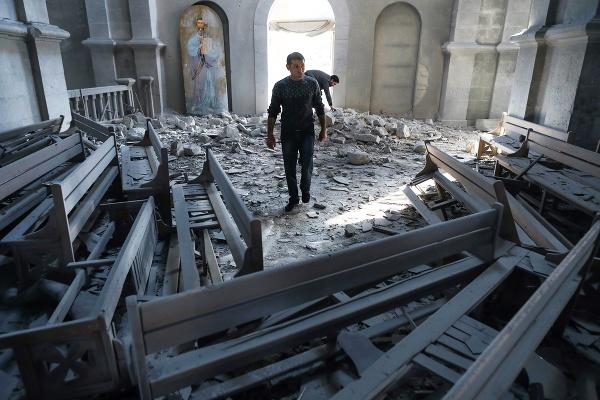 Muž kráča po ruinách