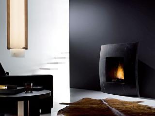 Čierny kozub, tmavá stena ikreslo sú vostrom kontraste soslnivobielym schodiskom. Pre horiaci ohník je tmavé pozadie ideálne. Vpohode kresla si možno vychutnať čiernu hodinku.