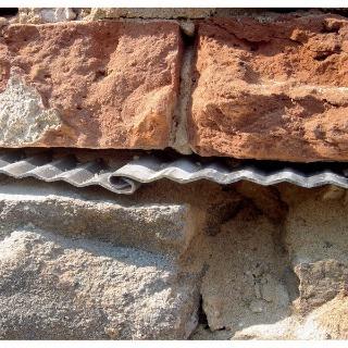 Detail dosák zarazených do steny