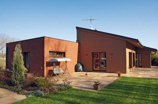 Zjužnej strany môžete vidieť iba najvyššie podlažie. Hmota domu sa delí na spoločný obývací priestor spultovou strechou aspálňovú časť splochou strechou apriznaným tehlovým obkladom. Veľké okná majú znížené parapety apevné zasklenie.