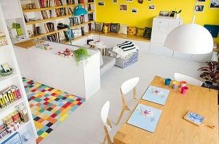 Svetlá podlaha, ktorá obývacej izbe dominuje, by pri neuváženom výbere ostatných povrchov adoplnkov mohla pôsobiť stroho achladne. Architekti ju však dostatočne vyvážili použitím teplých farieb na stenách ahravej dlažby vkuchyni.
