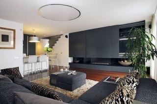 Neutrálny farebný základ, ktorý vytvorili kombináciou červenohnedej drevenej podlahy zexotického dreva, sivej abielej, dopĺňajú vobývacej časti zvieracie vzory na vankúšoch ahuňatý béžový koberec.
