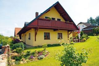 Štít spresahujúcou strechou vytvára rámec pre príjemný balkón pri rodičovskej spálni, zktorého jevýhľad na starostlivo udržiavanú záhradu.