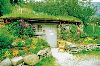 Záhradný domček môže byť vytvorený aj vo svahovitej záhrade. Namiesto strechy rastie tráva avstupné časti spríjemňujú rastliny. Slnečné miesta sú vhodné na pestovanie letničiek, ktoré kvitnú do neskorej jesene. Každoročne si tento priestor možno vysadiť