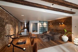 Drevené obloženie, ktoré definuje obývaciu časť prostredníctvom pokrytej steny a dlážky, je vyhotovené zo 150-ročných podlahových dosiek z nemeckých borovíc, ktoré sa pôvodne nachádzali pod dlážkou kancelárií.