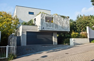 Trojpodlažný rodinný dom má od ulice odstup, aby nezatienil stavbu na susednom pozemku – vďaka tomu je pred garážou v úzkej ulici väčší manévrovací priestor.