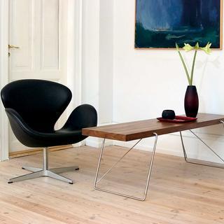Kreslo Swan Aarneho Jacobsena susedí so stolíkom Ad-Just. Kovová kostra stolíka ohybom prechádza do dreveného masívu. (foto: Add Interior)
