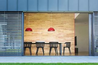 STENA OBLOŽENÁ AGÁTOVÝM DREVOM v jedálenskej časti domu od dizajnérov z Mio architects