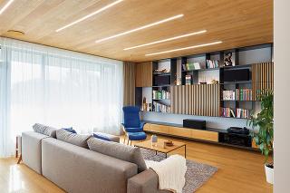 Vstavaná obývačková stena po uzatvorení nedáva tušiť, že je tu ukrytý televízor. Aby ste ho odhalili, stačí jednoducho odsunúť dvierka svertikálnymi dubovými lamelami osadenými na antracitovej doske.