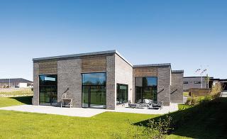 Tehlová fasáda doplnená dreveným obložením pôsobí príjemne domácky atradične. Moderný prvok prinášajú kontrastné čierne rámy okien adverí vedúcich na terasu. Hoci sa dom technickým riešením hlási kvýstavbe budúcnosti, jeho vzhľad aj vnútorné prostredie