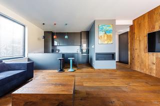 Brúsený dub sa zpodlahy plynule tiahne aj na ďalšie steny vbyte. Teplé drevo achladnejšia sivá farba sa vzájomne vynikajúco dopĺňajú anavodzujú vpriestore dojem elegancie.