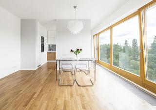 Jedálenský stôl je v obývacej časti miestnosti, prisadený k deliacej stene, za ktorou sa skrýva kuchyňa.
