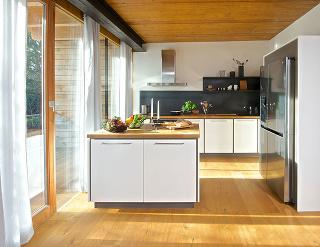 Biely MAGIQ z akrylu dopĺňa sivý a svetlý odtieň dubového dreva, ktoré sa opakujú v celom dome.