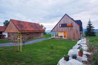 """Dom má jednoduchý pôdorysný tvar obdĺžnika asedlovú strechu so sklonom 45°, ktorú dopĺňa vikier so sklonom 6°. Archetypálnym tvarom, ktorý reaguje na historicky overenú formu, sa moderná drevostavba veľmi dobre začlenila medzi okolité staršie tradičné """"c"""