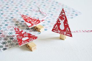 Štýlové stromčeky sú veľmi jednoduché na výrobu. Zpapierovej lepenky alebo kartónu vystrihnite trojuholníky. Rovnaké vystrihnite aj znejakého zvyšného vianočného baliaceho papiera avzájomne ich zlepte. Dbajte na to, aby lepenka nepretŕčala, nevyzerá to