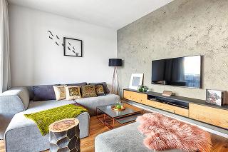 MIX VZOROV AMATERIÁLOV dodáva obývačke to pravé teplo domova akontrastuje schladnejším industriálnym nádychom, ktorý sem vnáša betónová stena. Orientálne vankúše si majiteľka priniesla zciest aobraz na stene je nápadom zjej hlavy. Skrátka, všade cít
