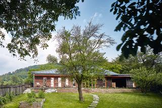 Vzhľad domu apoužité materiály vyplynuli zo samotnej parcely smohutným gaštanom rastúcim vzáhrade – architekti poňali drevenú stavbu ako akúsi parafrázu na vylúpnutie gaštanu zostnatej zelenej šupky.