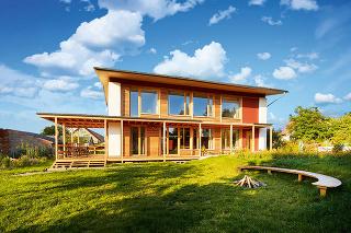 Drevené hranoly vytvárajú prevetrávanú medzeru pod zelenou strechou sfotovoltickými panelmi. Tie isté hranoly zároveň vytvárajú presah, ktorý tieni zasklené plochy domu.