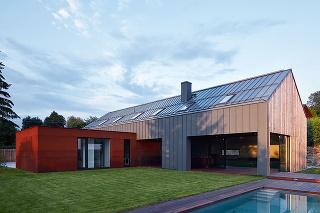 Vzhľad domu vychádza ztvaroslovia tradičných vidieckych stavieb so sedlovou strechou adreveným štítom, zároveň však pôsobí jednoznačne súčasne. Vpôdorysnom tvare kríža sa pretínajú dve odlišné hmoty – dvojpodlažná so sedlovou strechou, obložená sivým p