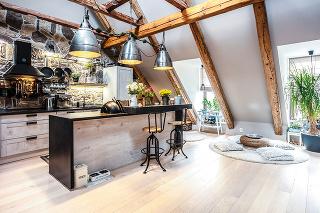 Otvorený denný priestor zaberá veľkú časť spodného podlažia podkrovného mezonetu. Dominuje mu kuchyňa spriestranným ostrovom doplneným barovým pultom, ktorý tu plní funkciu jedálenského stola. Kamenný obklad steny za linkou ladí so starými trámami zrekon