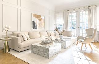 V obývačke majú svoje miesto dominantné mramorové konferenčné stolíky, rohová sedačka a vysoké kreslo s plyšovým poťahom.